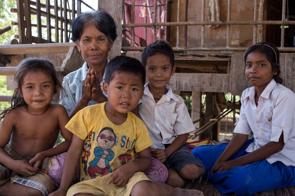 Mrs. Yong Pom and her grandchildren. Before the Community Water Treatment plant opened Mrs. Yong spent $10-15 per month on medicine. Now she spends far less than that on treated water.