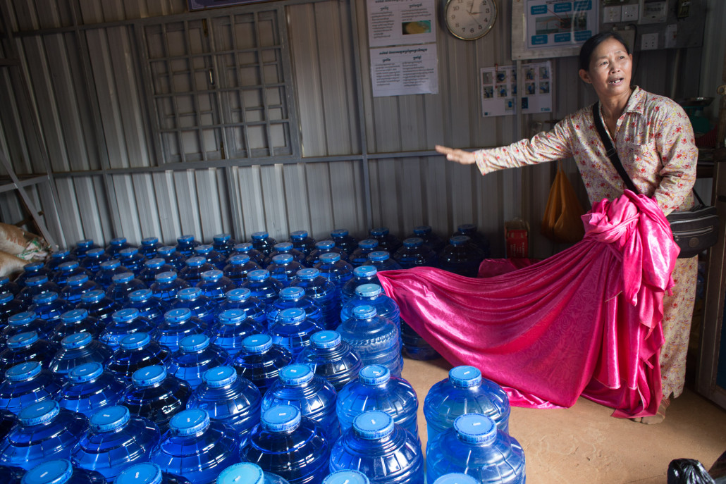 Mrs. Si Mean showing the bottles of treated water