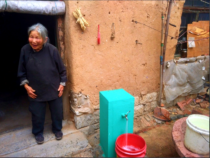 A villager in Zhujiazhuang village, Shandong province now has access to clean piped water right outside her home