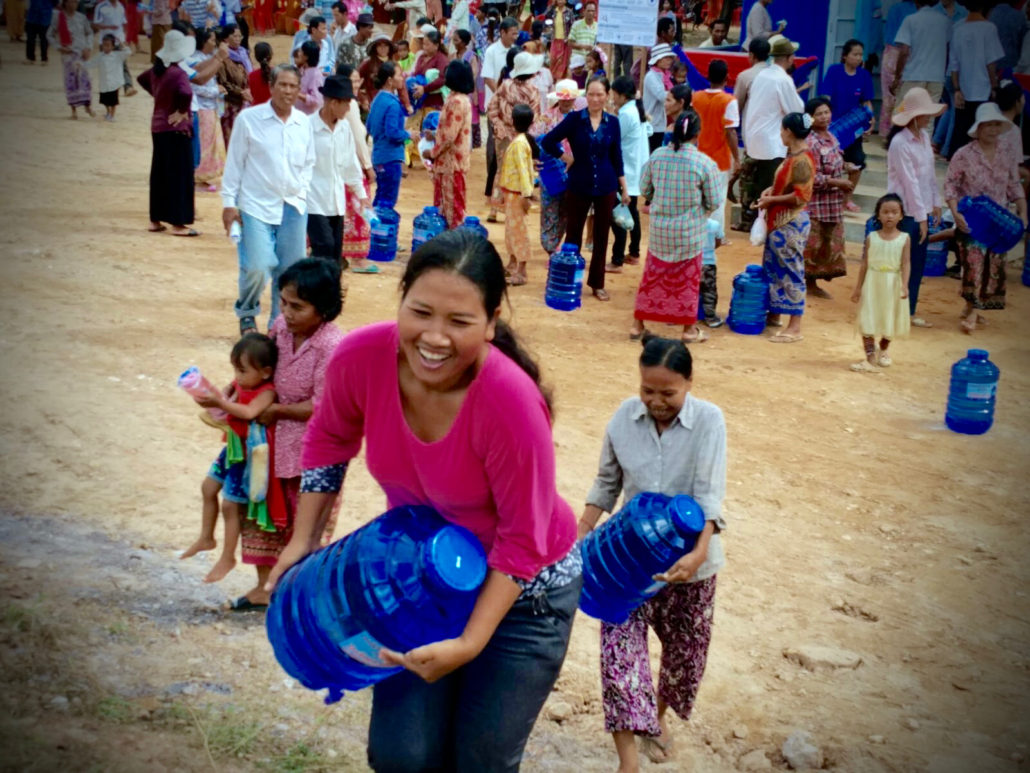 A villager carrying a new bottle of clean water purchased at the CWE handover event in Kdul Village, Cambodia.